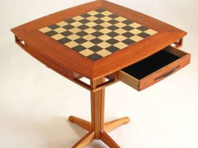 """Koa Games Table Chess or Checkers? Koa & Maple Top measures: 27"""" x 27"""" Table Height: 29"""" Board size: 17"""" x 17""""  featuring Holly and black dyed Anigree squares Two Maple and Koa accent drawers offer ample storage for game pieces. Drawer size: 13.25"""" x 11.75"""" x 1.5"""""""
